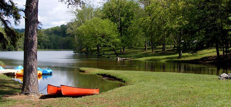 best kid friendly camping locations in ohio, picture of shawnee state park in ohio of a lake with canoes chained to a tree on a gorgeous day