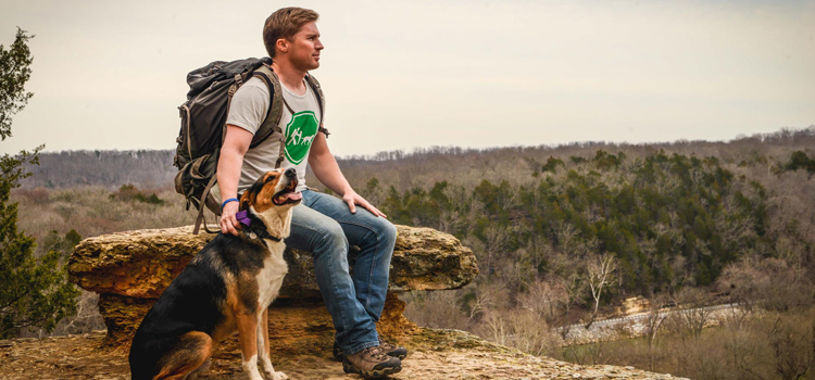 camping with dogs during a night hike, picture of a man and a dog sitting on a rock after a hike, how to camp with dogs at night