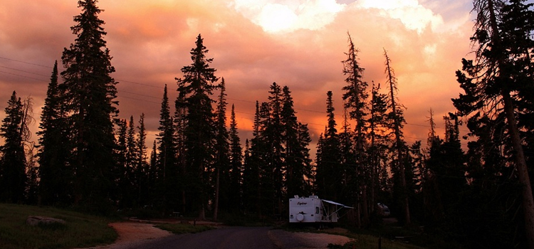 tips for your first rv camping trip, picture of a rv sitting outside during an orange sky with pine trees in the background