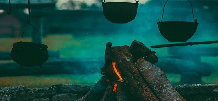 effective camping hacks, camping hacks, camping tips, picture of a camp fire with bowls cooking over top of the fire