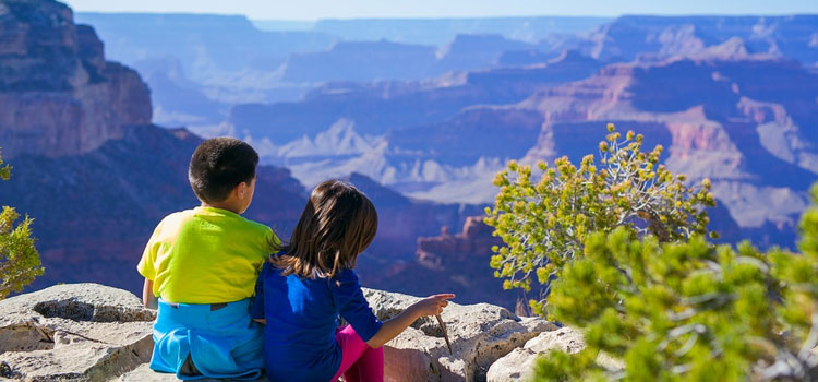 respect the environment, picture of 2 kids sitting on the top of a mountain enjoy a gorgeous view of mother nature, how to teach children to respect the environment while camping